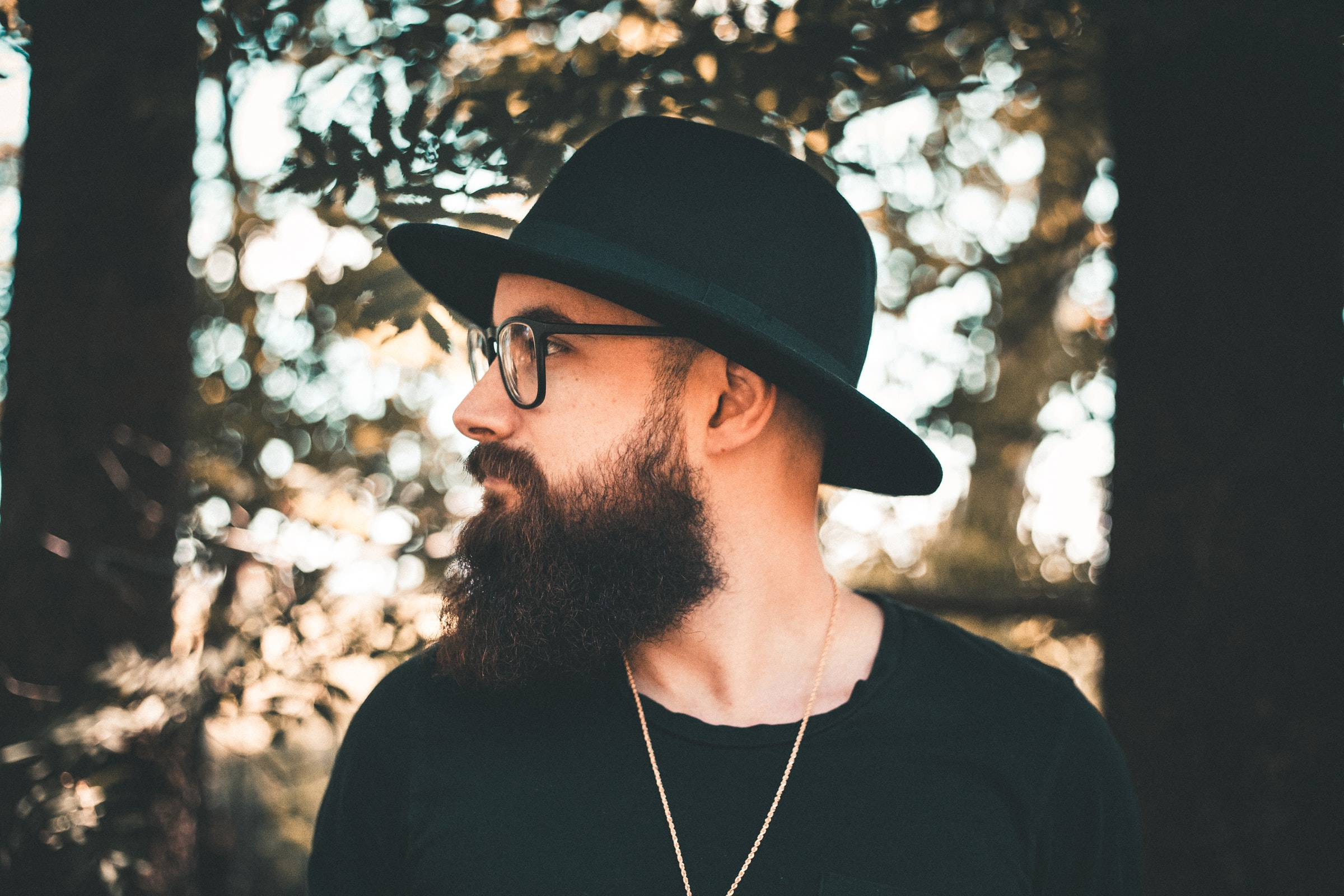 Man wearing black bolwer hat looking to his right with a thick beard wearing a black t shirt and glasses in the forest