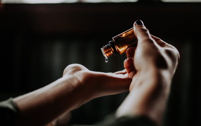 Person putting drops of essential oil on hands